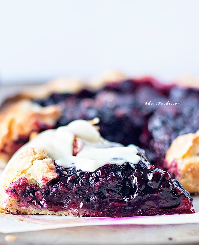 Delicious Rustic Berry Tart, packed with fragrant berry flavors in crispy, rough pastry served with vanilla custard!