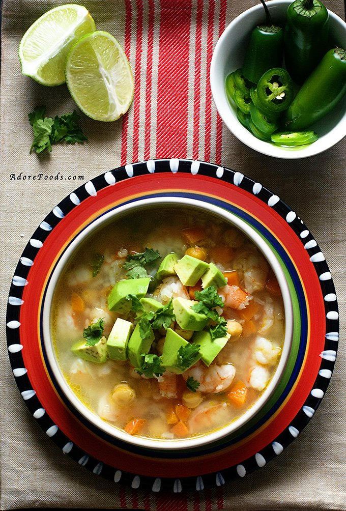 Authentic Mexican Seafood Soup with shrimp, carrots and beans in a spicy smoky adobo broth, served with avocado pieces and jalapeño peppers on side